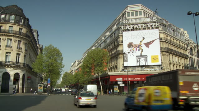 ws traffic outside galleries lafayette, paris, france - tabellone video stock e b–roll