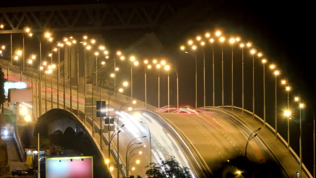 traffic over bridge at night time lapse - telephoto lens stock videos and b-roll footage