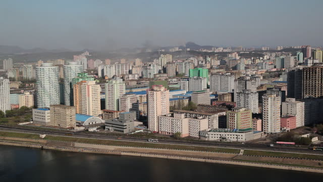 traffic passes a block of apartment buildings and the taedong river. - pyongyang stock videos and b-roll footage