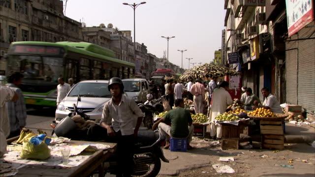 traffic passes a busy food market. - デリー点の映像素材/bロール