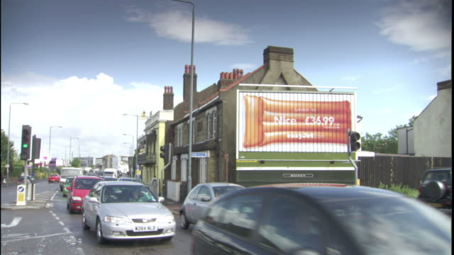 vídeos de stock e filmes b-roll de traffic passes a digital billboard in london. - billboard