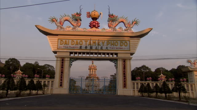 traffic passes a gate leading to cao dai temple. - tay ninh stock videos & royalty-free footage