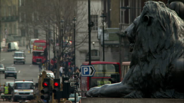 traffic passes a lion statue in trafalgar square, london. - big cat stock videos & royalty-free footage