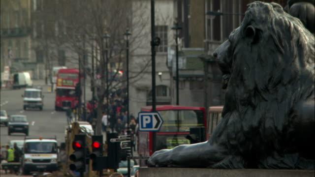 traffic passes a lion statue in trafalgar square, london. - trafalgar square stock videos & royalty-free footage