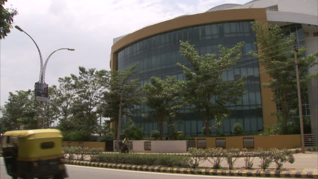traffic passes a modern glass office building in bangalore, india. - bangalore stock videos and b-roll footage
