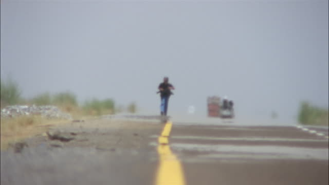 traffic passes a photographer as he walks along the shoulder of a road. - yemen stock videos and b-roll footage