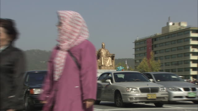 Traffic passes a statue of Sejong the Great in Seoul.