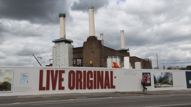 Traffic passes along road on north bank of the River Thames as Battersea power station stands in the background in the Nine Elms district of London...
