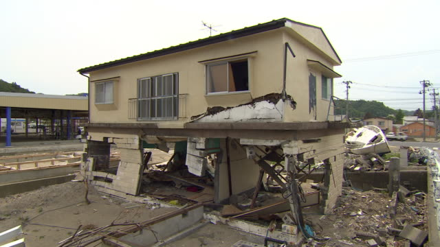 traffic passes behind a devastated house. - 自然災害点の映像素材/bロール