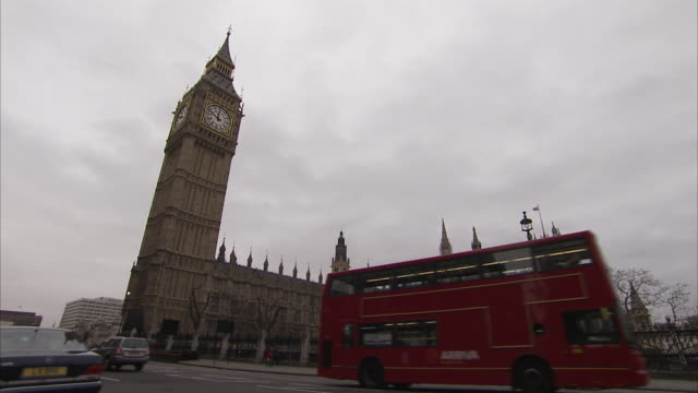 Traffic passes below London's Big Ben at the Houses of Parliament on a cloudy day. Available in HD.