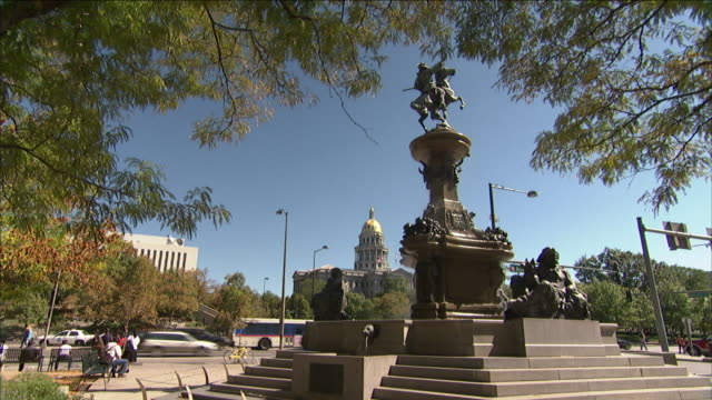 vidéos et rushes de traffic passes between thecolorado state capitol and smoky hill trail monument in denver. - colorado