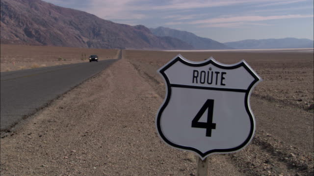 traffic passes by a road sign in death valley. - death valley stock-videos und b-roll-filmmaterial