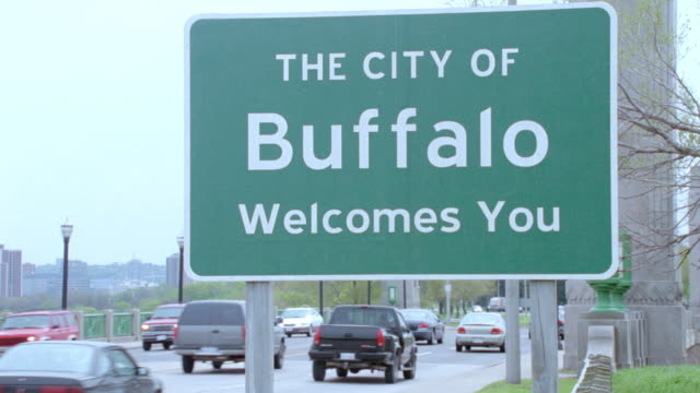 traffic passes by a welcome sign upon entering buffalo, new york. - road sign stock videos & royalty-free footage