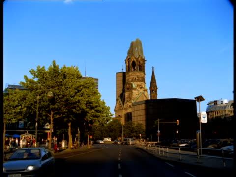 vídeos y material grabado en eventos de stock de traffic passes in front of kaiser wilhelm memorial church in berlin. - iglesia conmemorativa del emperador guillermo