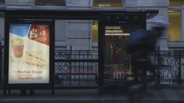 traffic passes london bus stop - tabellone video stock e b–roll