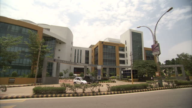 traffic passes office buildings in bangalore, india. - bangalore stock videos and b-roll footage