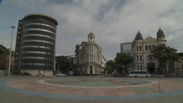traffic passes old and modern buildings on a plaza in recife, brazil. - recife stock videos and b-roll footage