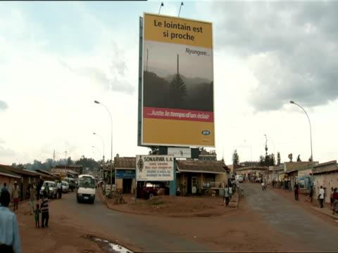 ws traffic passes on either side of huge billboard advertising nyungwe forest national park / nyamirambo, kigali, rwanda - キガリ点の映像素材/bロール