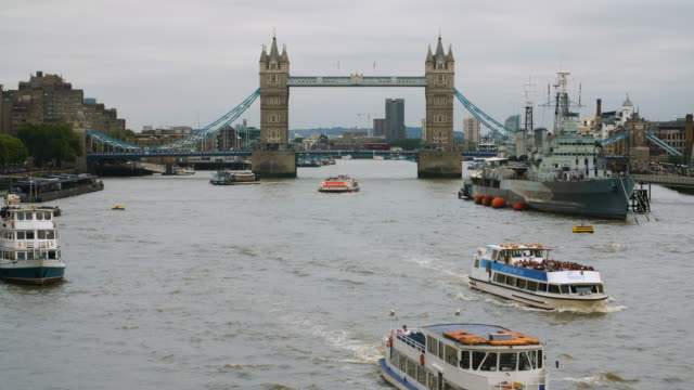 vídeos de stock, filmes e b-roll de traffic passes over tower bridge as boats pass on the river thames - nublado