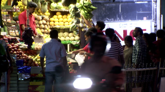 Traffic passes shoppers at a produce stand in Bangalore, India.