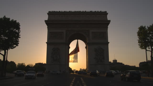 vídeos de stock e filmes b-roll de traffic passes the arc de triomphe in paris, france. - arco caraterística arquitetural