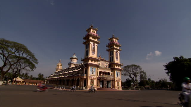 traffic passes the cao dai temple. - tay ninh stock videos & royalty-free footage