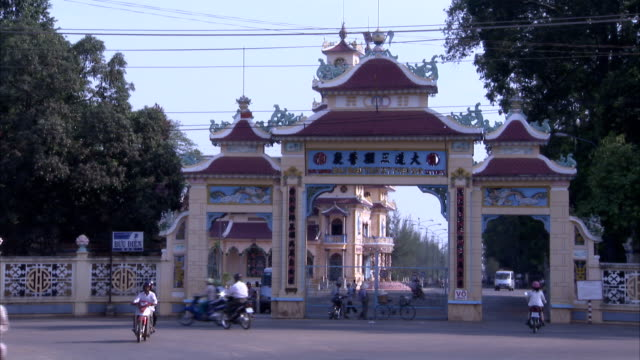 traffic passes the outer gate leading to the cao dai temple. - tay ninh stock videos & royalty-free footage