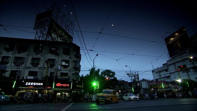 traffic passes through an intersection at night. - kolkata stock videos & royalty-free footage