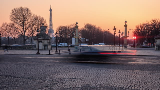 Traffic passes  with the Eiffel Tower in sunset