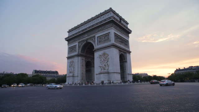 traffic passing around arc de triomphe at twilight, paris, france - triumphal arch stock videos & royalty-free footage