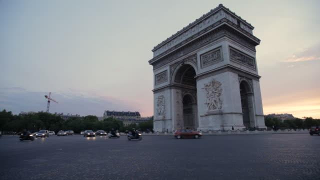 Traffic passing around Arc de Triomphe at twilight, Paris, France
