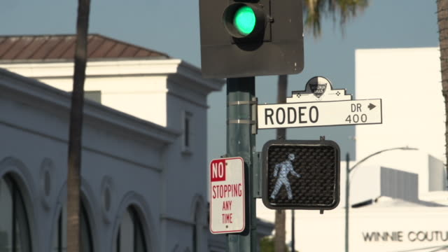 traffic passing beneath the rodeo drive street sign, beverly hills california - glamour stock videos & royalty-free footage