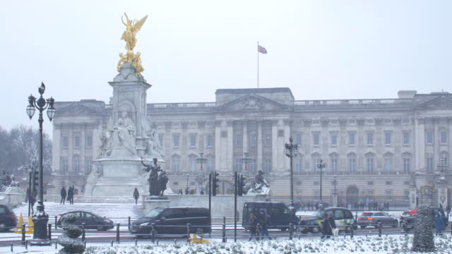 traffic passing buckingham palace in the snow. - england stock-videos und b-roll-filmmaterial