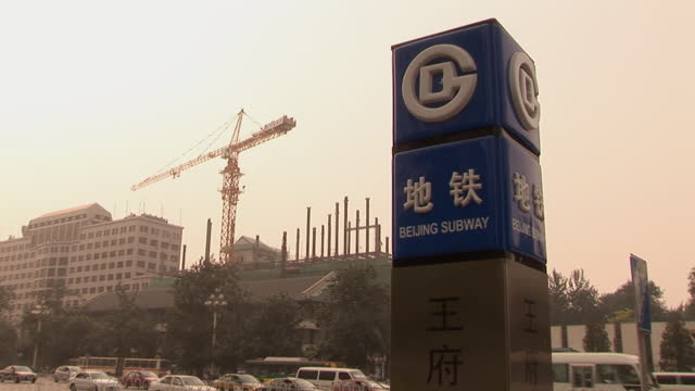 ws traffic passing by subway entrance with construction crane in background/ beijing, china - non western script stock videos & royalty-free footage