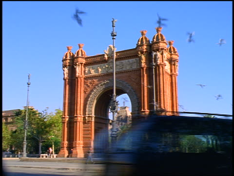 Traffic passing in front of + birds flying from Arc del Triomf in square / Barcelona, Spain