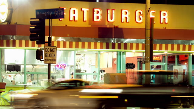 ms t/l traffic passing in front of fast food restaurant serving burgers / los angeles, california, united states - in front of stock videos & royalty-free footage