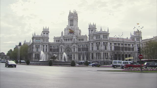 stockvideo's en b-roll-footage met ws traffic passing in front of palacio de comunicaciones, now known as madrid city hall / madrid, spain  - town hall