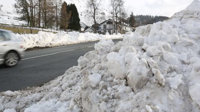 traffic passing large snowdrifts on the a591 road at thirlmere in the lake district, uk, following the unseasonal extreme weather events of late... - deep snow stock videos & royalty-free footage
