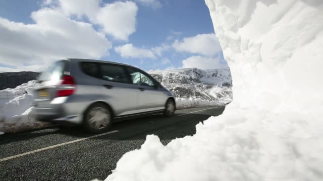 traffic passing large snowdrifts on the A591 road at Thirlmere in the Lake District, UK, following the unseasonal extreme weather events of late march 2013.