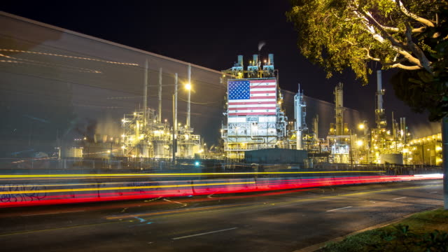 Traffic Passing Oil Refinery with American Flag - Time Lapse