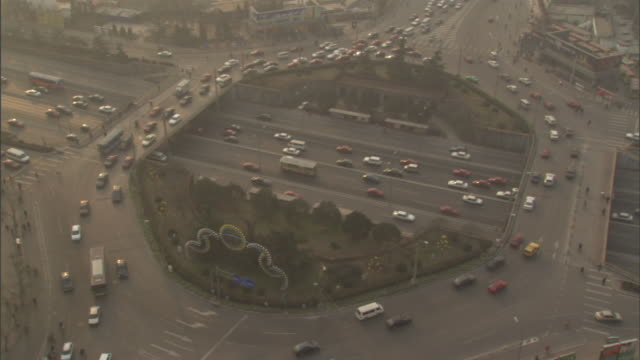 WS HA Traffic passing on circular ramp and on highway below on smoggy day, Beijing, China