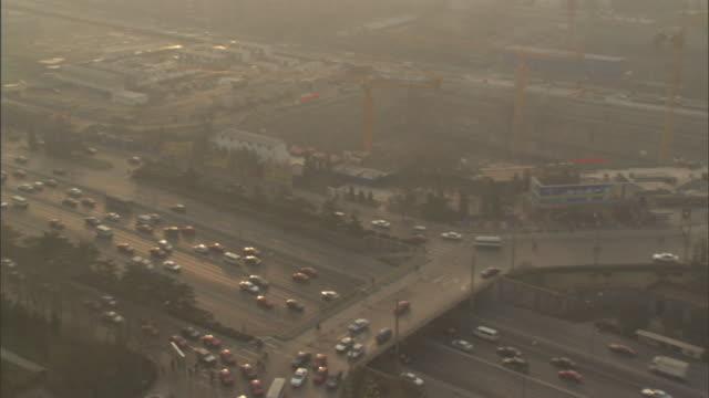 ws ha pan traffic passing on circular ramp and on highway below on smoggy day, beijing, china - スモッグ点の映像素材/bロール