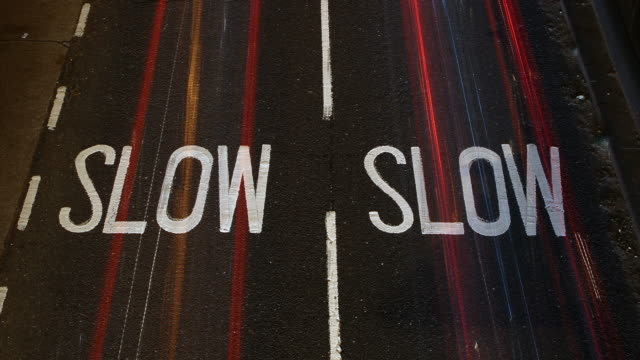 ha t/l traffic passing over 'slow' sign in the road. - single word stock videos & royalty-free footage