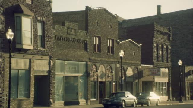 WS Traffic passing storefronts on old-fashioned small town street/ Buffalo Ridge, Minnesota