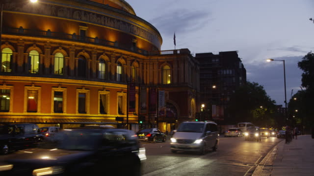 traffic passing the royal albert hall at sunset. - royal albert hall stock videos and b-roll footage