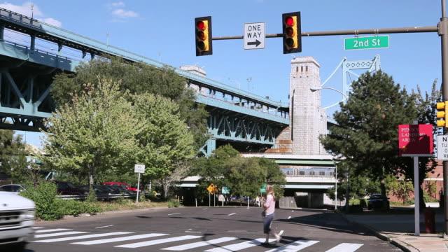 ws traffic passing through a city intersection in front of the benjamin franklin bridge / philadelphia, pennsylvania, united states - ベンフランクリン橋点の映像素材/bロール