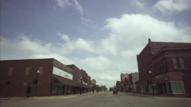 WS Traffic passing through downtown intersection as clouds move overhead/ Pipestone, Minnesota