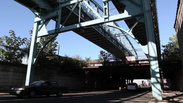 la traffic passing through shadows under an elevated train bridge / philadelphia, pennsylvania, united states - ベンフランクリン橋点の映像素材/bロール