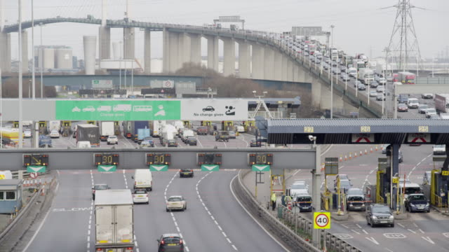 vidéos et rushes de traffic passing through tolls booths on the dartford river crossing. - traverser