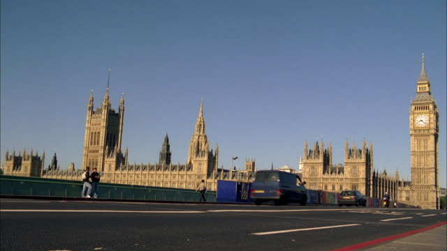 la traffic passing westminster palace and big ben / london, england, united kingdom - victoria tower stock videos & royalty-free footage